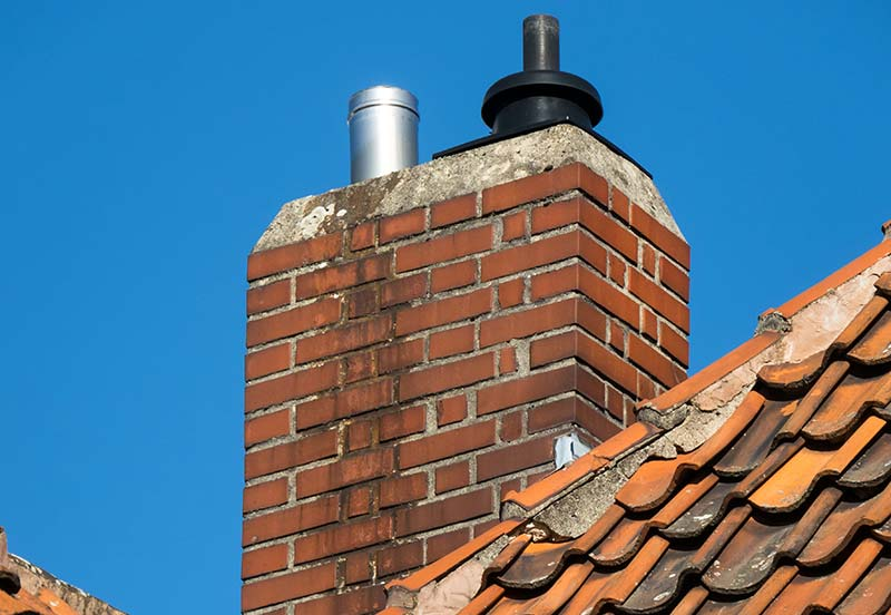 Small Red Brick Chimney On Top Of A Sloped Shingle Roof