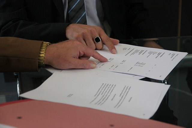 Two People Reviewing A Contract Agreement Together