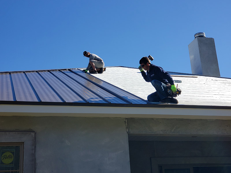 Prime Roofing Crew On Top Of Metal Roof