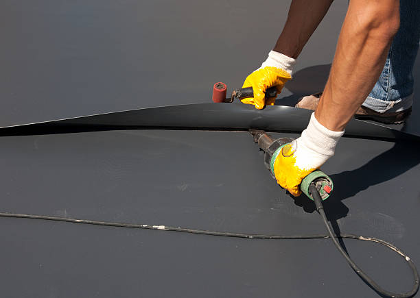 Roofer Installing Coating On Residential Roof