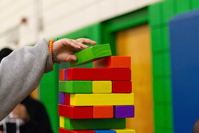 young child playing with tower stacking toys